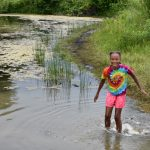 A camper cools off by talking a splash in the pond at Highbanks' Dragonfly Day Camp. (Virginia Gordon)