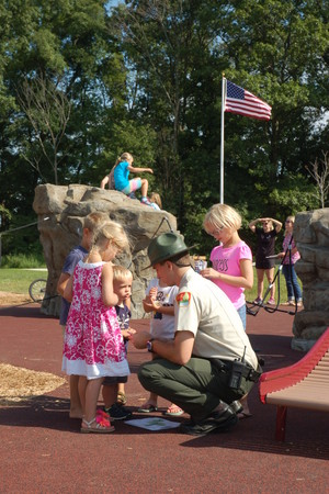 Bryan Knowles Photographer. Taken 8/14/2015. Ranger Brandon Novotny passing out stickers to children on the playground at Rocky Fork Metro Park.