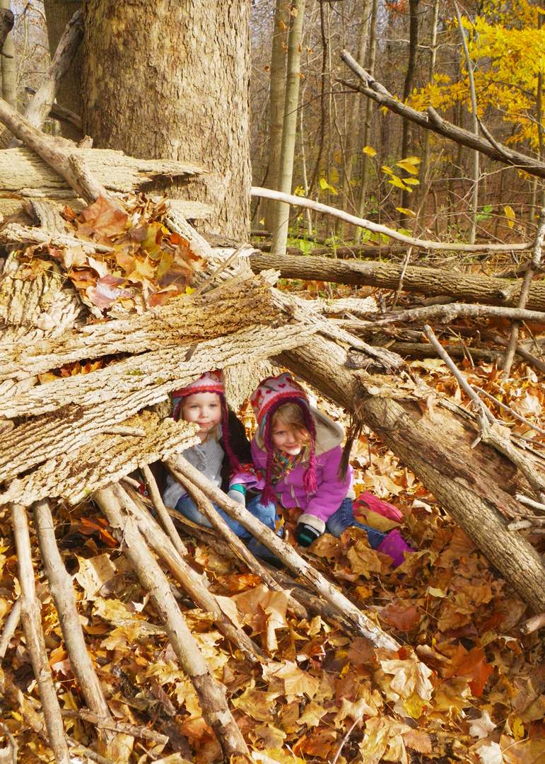 Two girls shelter inside their fort in the natural play area at Sharon Woods. Allison Shaw
