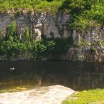 Canoe floats by the cliff face at Quarry Trails