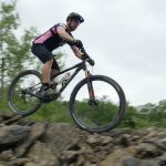 A mountain biker rides over rocky terrain at Quarry Trails