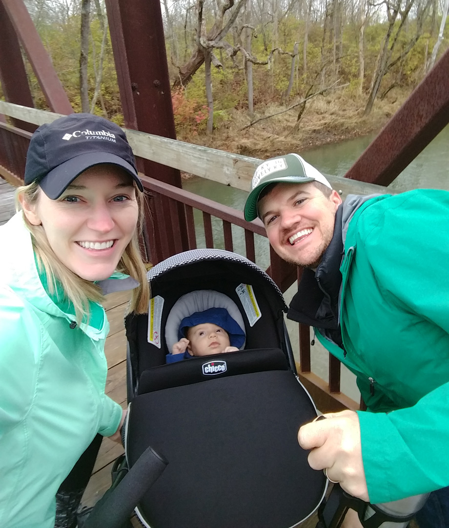 Young couple and their baby pose for photo on bridge over Big Darby Creek