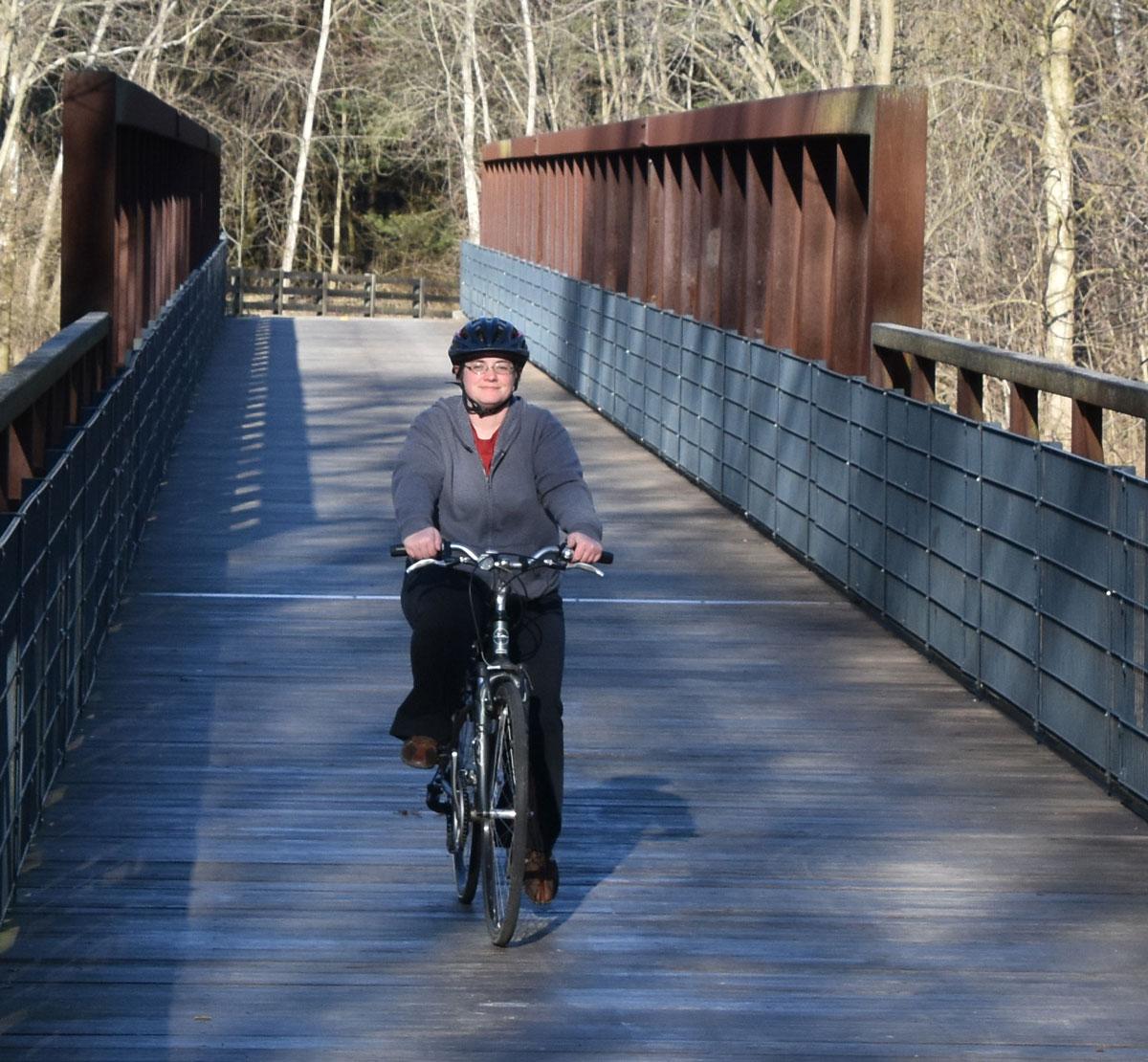 Biker crosses Big Walnut Creek on a bridge in Three Creeks Metro Park