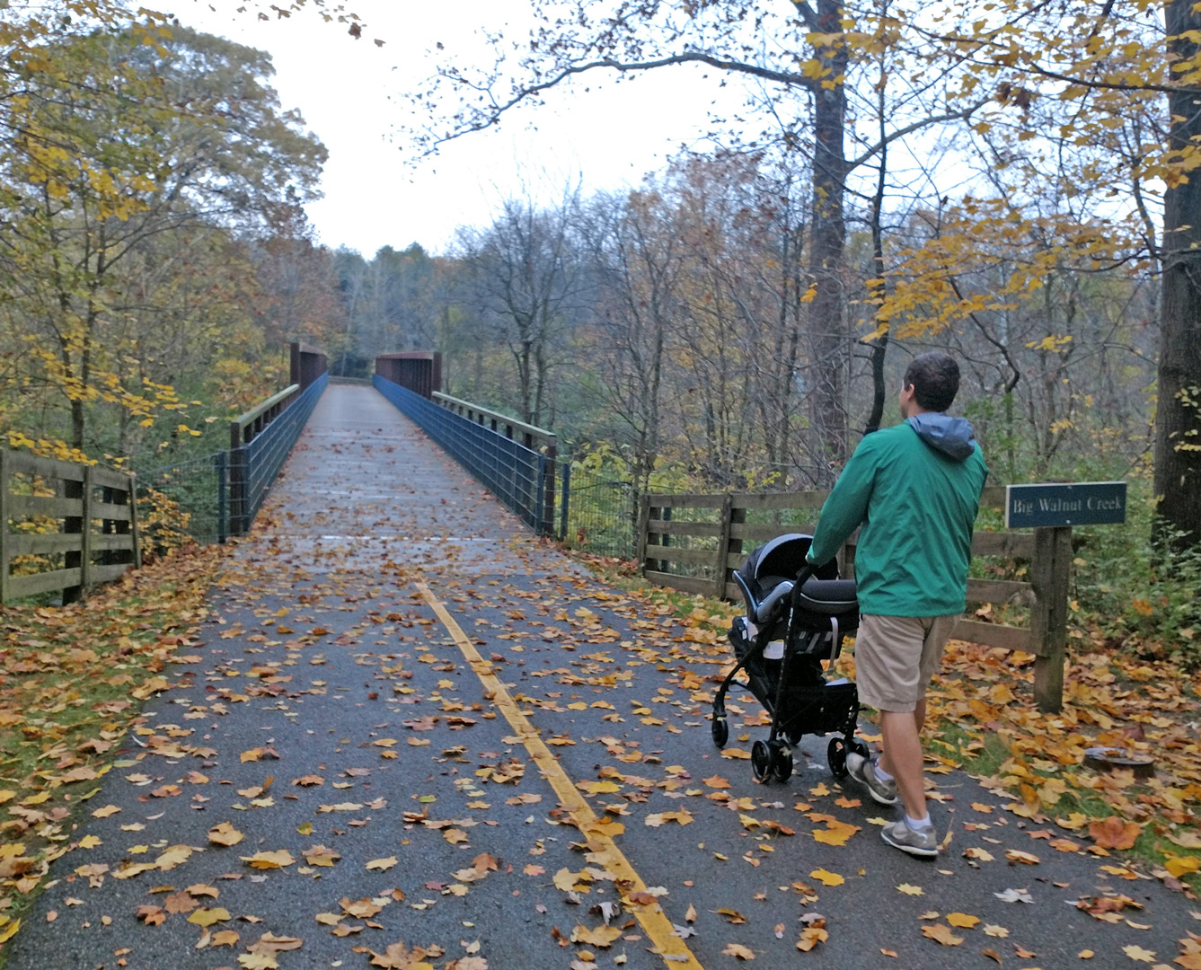 Young father pushes baby stroller across bridge over Big Walnut Creek at Three Creeks Metro Park