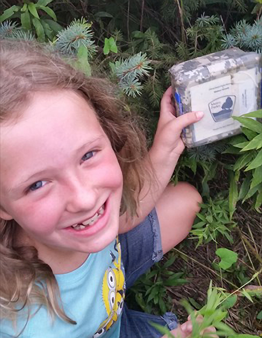 A young girl holds a geocaching box found on a geocaching at Metro Parks search at Walnut Woods Metro Park