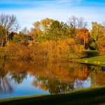 Autumn scene with reflections of colorful trees in water of the fishing pond at Homestead