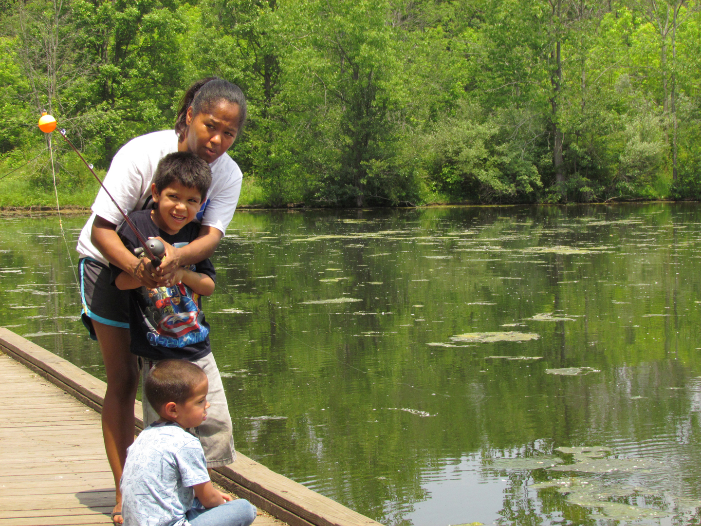Adult helps young boy cast a fishing line into Schrock Lake at Sharon Woods Metro Park