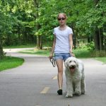 A girl walks her dog on the Greenway Trail at Three Creeks Metro Park
