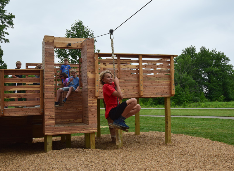 A kid takes off on the zipline on a play structure at Glacier Ridge.