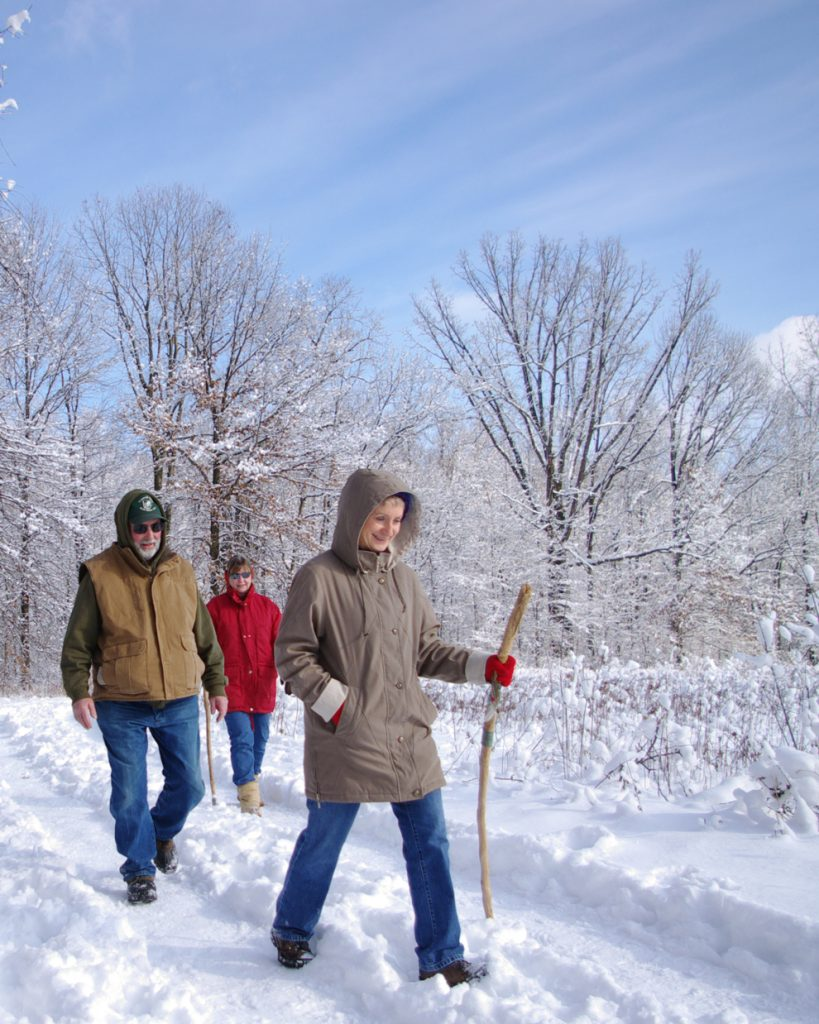 Three hikers walk along a snowy trail at Blendon Woods
