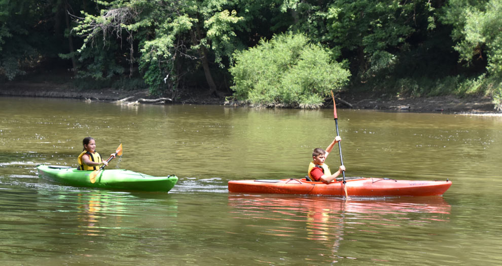 Summer campers in two kayaks float down the Scioto River at Scioto Grove Metro Park