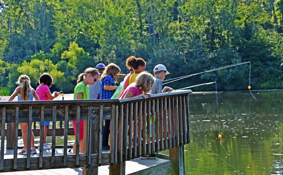 Group of kids fish from a deck over the pond at Highbanks Metro Park