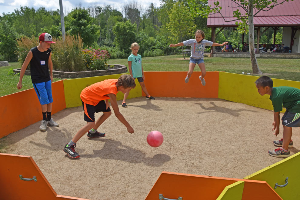 A group of kids play a game of gaga ball in a circular play arena