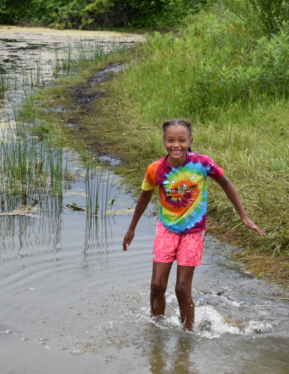 A girl on a summer camp cools off in the pond at Dragonfly Day Camp in Highbanks