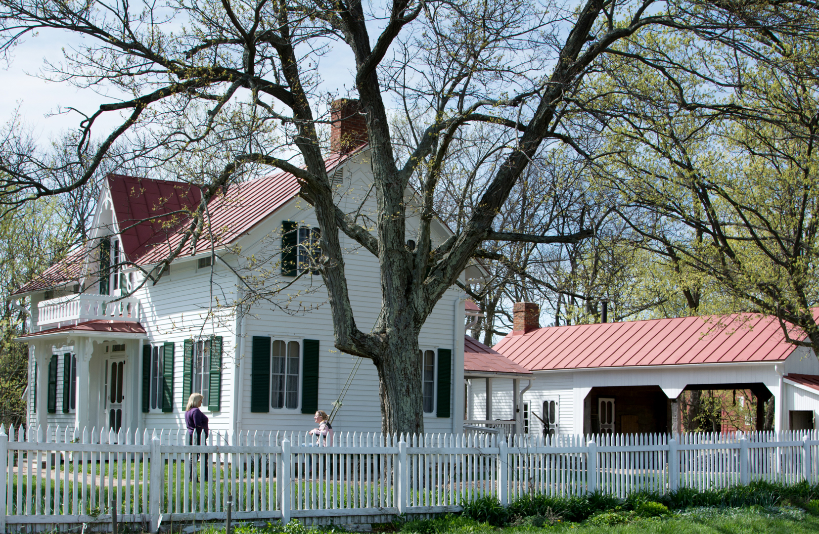 Farmhouse at Slate Run Living Historical Farm, with a girl on the swing