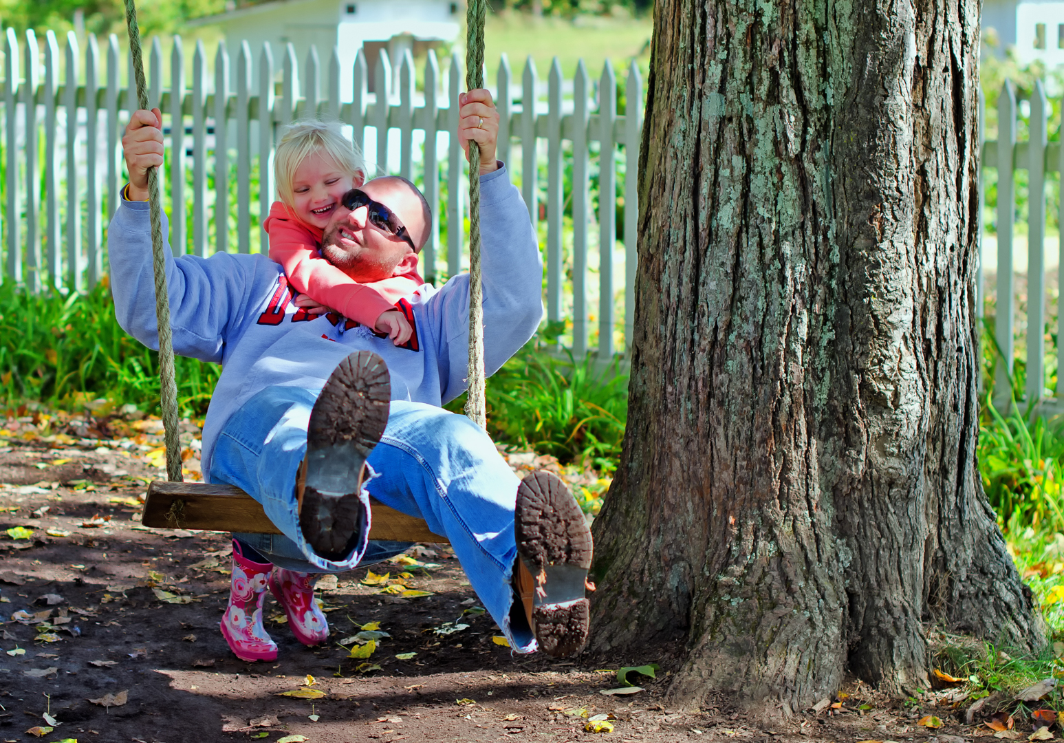 A father and daughter have fun on the swing outside the farmhouse at Slate Run Living Historical Farm. The swing is attached to the branch of a silver-maple tree.