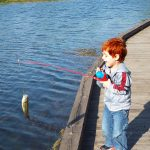Boy catches a bass in the fishing pond at Chestnut Ridge
