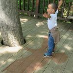 A boy measures his wingspan against that of an eagle, painted on the wooden deck behind the nature center at Highbanks