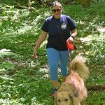 Woman walks her dog in the woods at Scioto Grove Metro Park