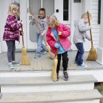 Visitors sweep the steps at at the farmhouse during a program at Slate Run Living Historical Farm
