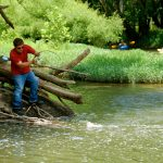 Fisherman catches a fish in Big Darby Creek as kayakers approach in the distance