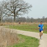 Runner and hiker on Darby Creek Greenway Trail at Battelle Darby Creek