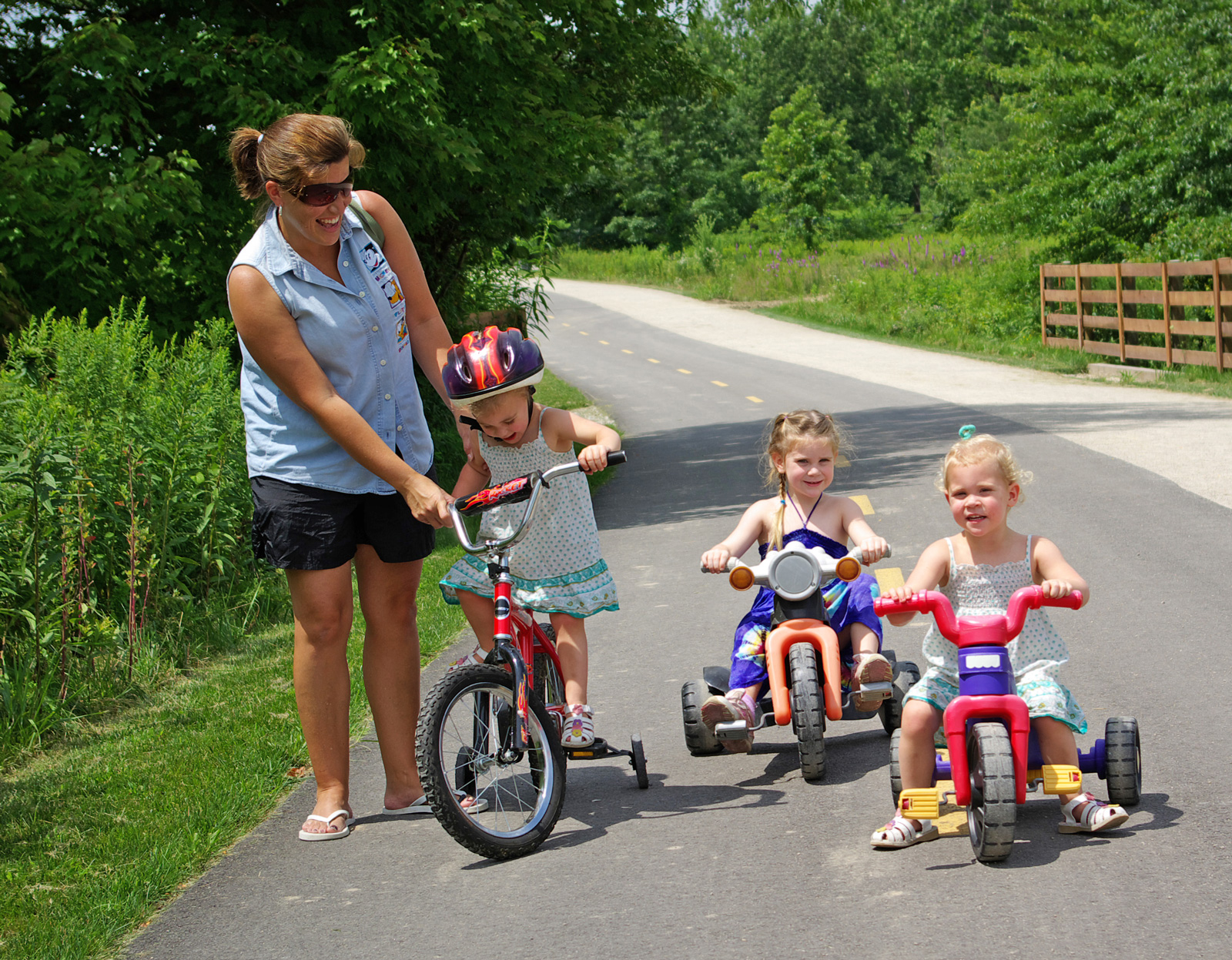 Three young tricyclists with adult supervision on the Multi-use Trail at Blacklick Woods.