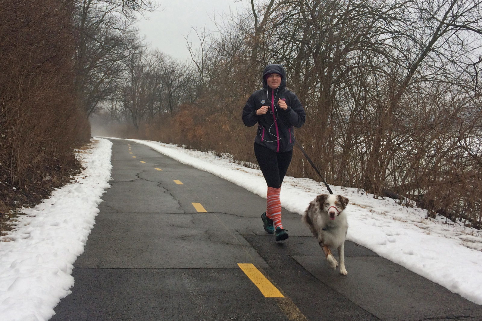 A woman and her dog run the Scioto Greenway Trail at Scioto Audubon.