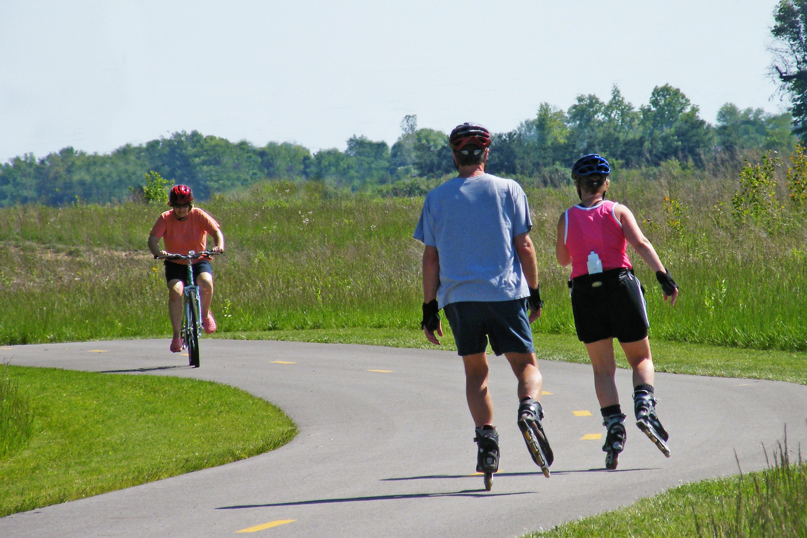 Roller-bladers and a cyclist about to pass each other on the Blacklick Creek Greenway Trail in the north west part of Pickerington Ponds.