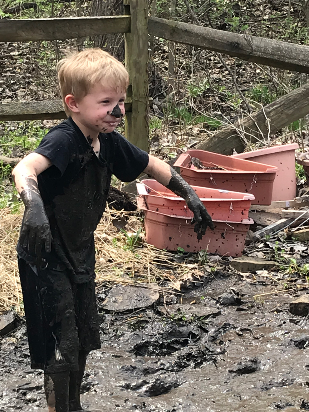 Young boy covered in mud at the Blendon Woods Natural Play Area.