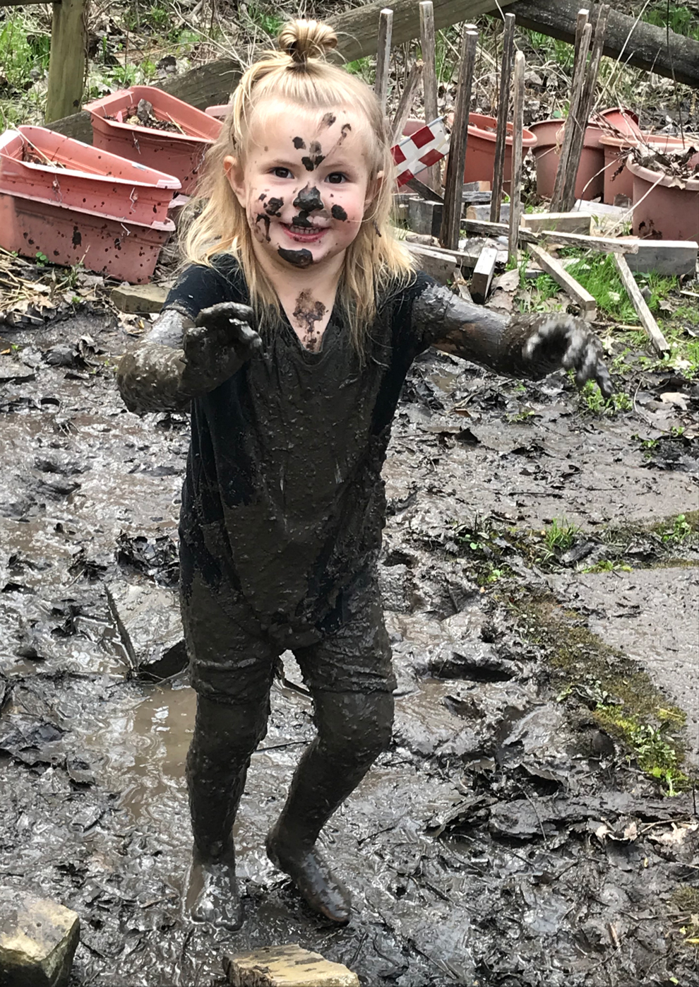 A young girl covered in mud at the Blendon Woods Natural Play Area