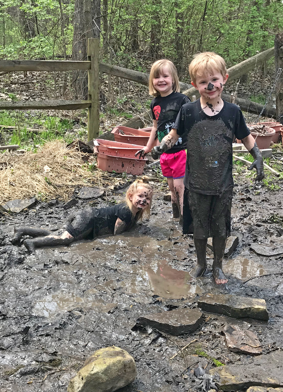 Three preschoolers get muddy in the natural play area at Blendon Woods.