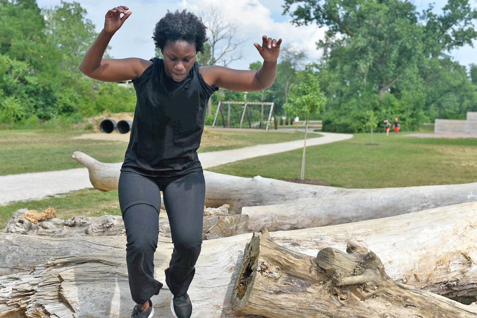 Woman on the log run on the obstacle course at Scioto Audubon Metro Park.