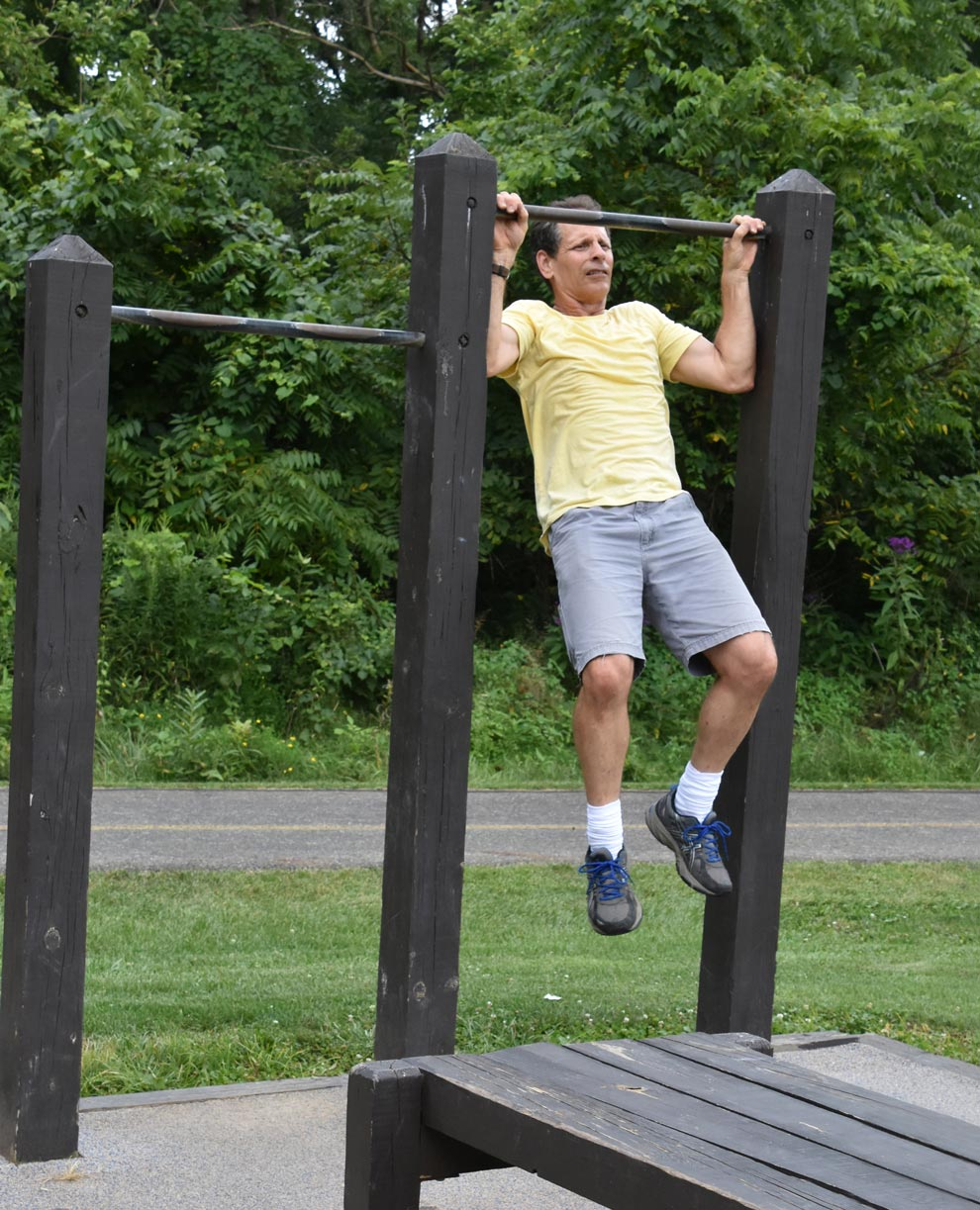 A man uses the pull-up bars at Sharon Woods' fitness station.