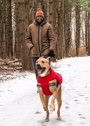 Man and dog walk on Sweetgum Trail at Walnut Woods Metro Park